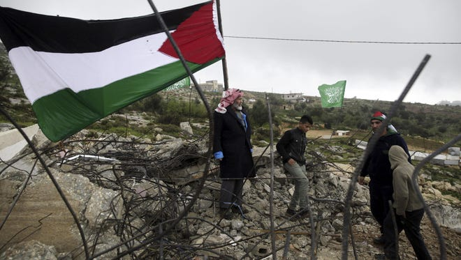 Palestinians stand next to their national flag and on the rubble of the demolished house of Raid Halil, who killed two Israelis in a stabbing attack in Tel Aviv in November, that was demolished by Israeli bulldozers, in the West Bank village of Dura, near Hebron, Tuesday, Feb. 23, 2016. Israel demolished the homes of two Palestinians who committed separate attacks against Israelis that killed five people, the military said. (AP Photo/Mahmoud Illean)