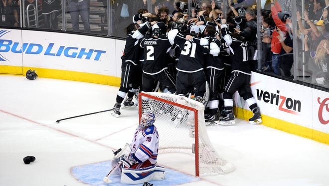 The Los Angeles Kings celebrate winning the Stanley Cup as Rangers goalie Henrik Lundqvist crouches in his goal.