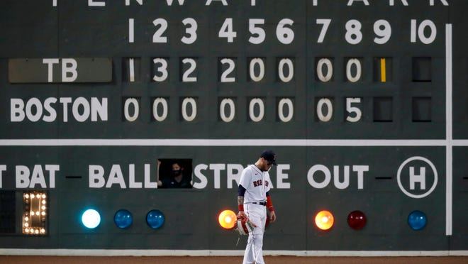 Boston Red Sox's Alex Verdugo stands in front of the left field scoreboard during the ninth inning of a baseball game against the Tampa Bay Rays, Wednesday, Aug. 12, 2020, in Boston.