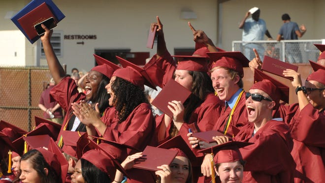 Seniors cheer a classmate on the stage at the 2015 Astronaut High School graduation, held Saturday morning, May 23,  at the Storey-Taylor Stadium at the school campus.