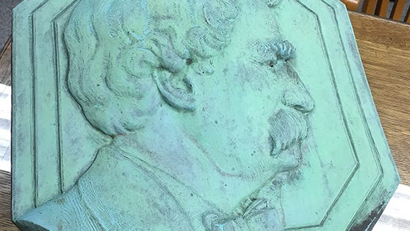 The Mark Twain plaque was removed in mid-December from a monument at Twain's gravesite in Woodlawn Cemetery in N.Y. Elmira police displayed the recovered plaque that had some damage from being pried from the monument.