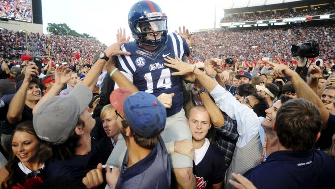 Mississippi  quarterback Bo Wallace (14) is carried off the field by fans following their 23-17 win over No. 3 Alabama.