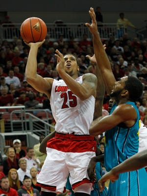 University of Louisville's Wayne Blackshear (25) fights to get his shot off under pressure from UNC Wilmington's Cedrick Williams (40) during the first half of play at the KFC Yum! Center in Louisville, Kentucky.       December 14, 2014.