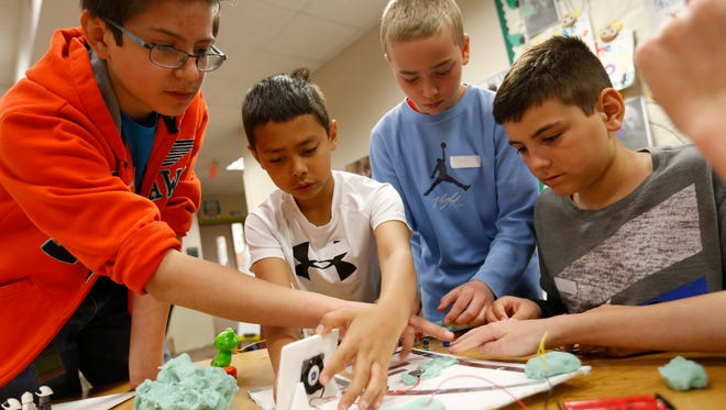 Thomas Richards, a sixth-grade helper from Clive Elementary (from left), gives fifth-graders Kai Smith-Bui, 10, Beau Longnecker, 11, and Jayden Hansen, 11, some tips on how to connect up their batter to a circuit board made of foil tape and putty during a Makers Fair on March 24 at Beaver Creek Elementary in Johnston.