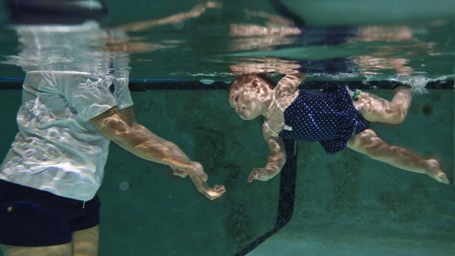 Kaybrick Gleason, 13 months, learns to roll under water with the guidance of Kathy Cole, an ISR Master Instructor (Infant Swimming Resource) during an infant self-rescue class Thursday morning (7/23/15) taught by Cole in the pool at Scubavice Dive Center in Fort Myers.