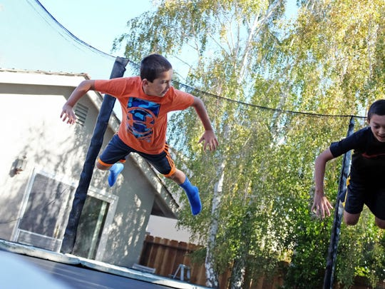 Evan Silacci, 9, left, and his brother Ethan, 12, are photographed in midair on their backyard trampoline. Evan was diagnosed with Multiple Sclerosis when he was 5 years old.