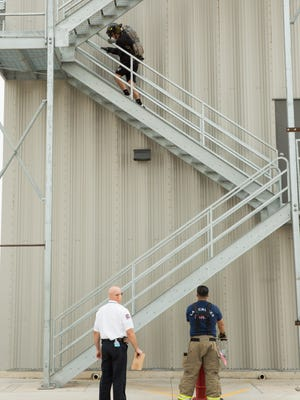 Ty Erramouspe, with the El Paso Rhinos, heads up the side of the Las Cruces Fire Department's training facility during the stair climb, part of the course the Rhinos went through. As Fire Training Officer Ron Schulmeister,left, and Fire Fighter Joshua Gonzales look on. Saturday, February 18, 2017.