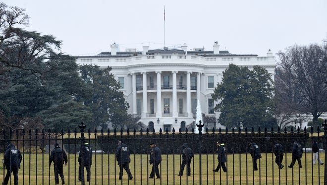 In this Jan. 26, 2015 file photo, Secret Service officers search the south grounds of the White House in Washington after an unmanned aerial drone was found on the White House grounds.