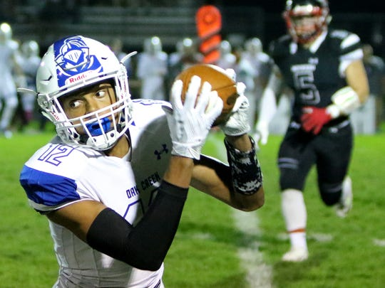 Oak Creek's James Carter Jr. spins upfield with a reception at Muskego on Oct. 20.