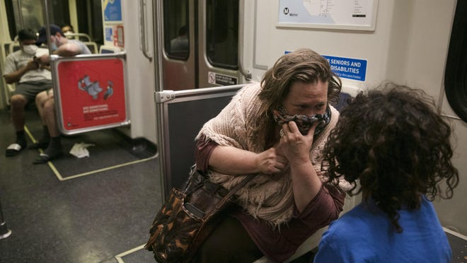 Lisa Fink holds a face covering to her mouth while talking to her son, Al, in a Metro Rail train on Monday in Los Angeles. The coronavirus is blamed for more than a half-million deaths worldwide, including more than 130,000 in the U.S., according to the tally kept by Johns Hopkins University.
