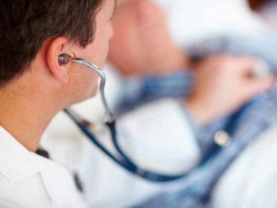 Doctor examining a patients heart beat with a stethoscope