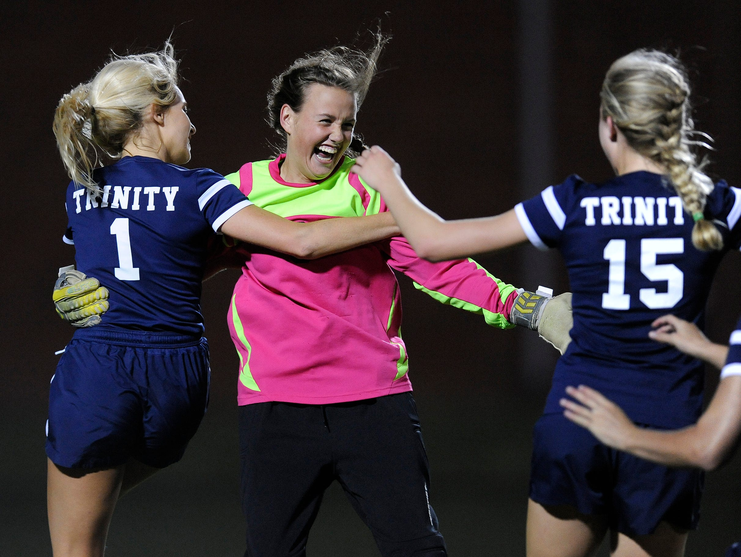Trinity's Lanier Sanders (1), Joy Bishop and Mary Stuart Tipton (15) celebrate the win over St. James at the St. James campus in Montgomery, Ala., on Tuesday April 28, 2015.