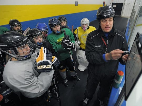 Leo Fusilli, right, reviews tactics with the team before practice.