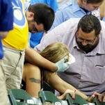 A woman is helped after being hit by a foul ball during the ninth inning of a game between the Milwaukee Brewers and the Atlanta Braves on Monday, July 6, 2015, in Milwaukee.