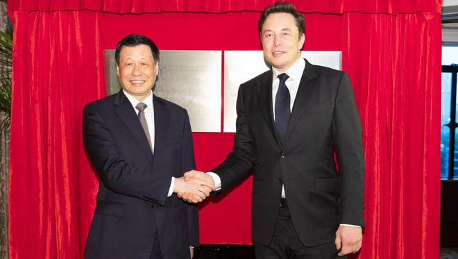 Tesla CEO Elon Musk (right) signs a deal with an unidentified official in China to build a new plant in Shanghai.