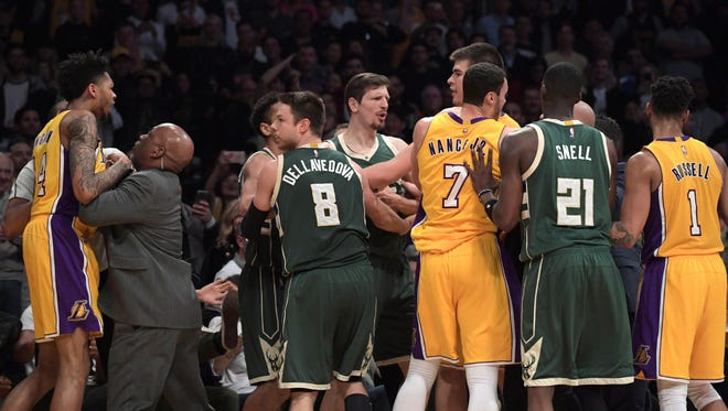 Los Angeles Lakers forward Brandon Ingram (14) and forward Larry Nance Jr. (7) and guard D'Angelo Russell (1) scuffle with Milwaukee Bucks guard Matthew Dellavedova (8) and guard Tony Snell (21) during a NBA basketball game at the Staples Center.