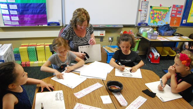 Kindergarten teacher Mary Axtell works with her students Wednesday at Millside Elementary in Algonac