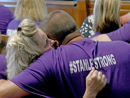 Family of victims embrace after Grate sentenced Friday.