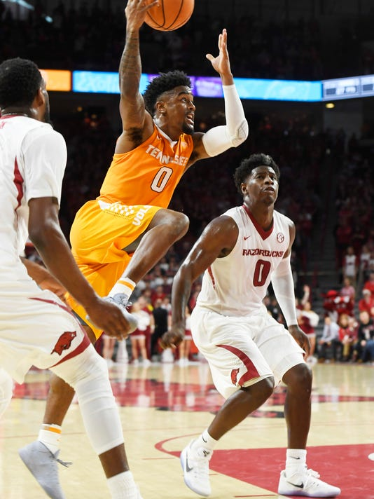 Tennessee guard Jordan Bone tries to drive to the hoop past Arkansas defenders Arlando Cook (5) and Jaylen Barford during the first overtime period of an NCAA college basketball game, Saturday, Dec. 30, 2017 in Fayetteville, Ark. (AP Photo/Michael Woods)