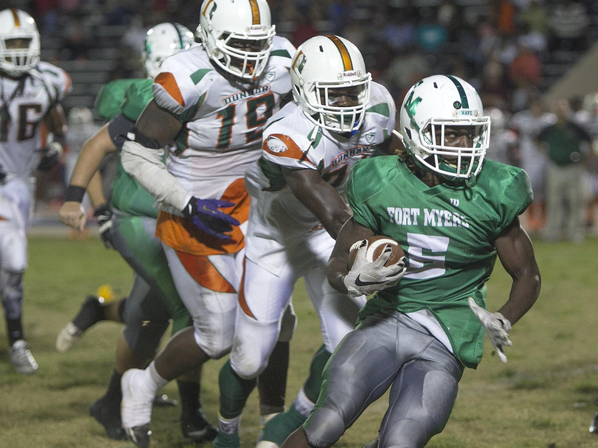 Fort Myers ball carrier Darrian Felix, right, leads Dunbar defenders Donovan Gayle and Shanon Reid as he sprints for positive yardage Friday in Fort Myers.