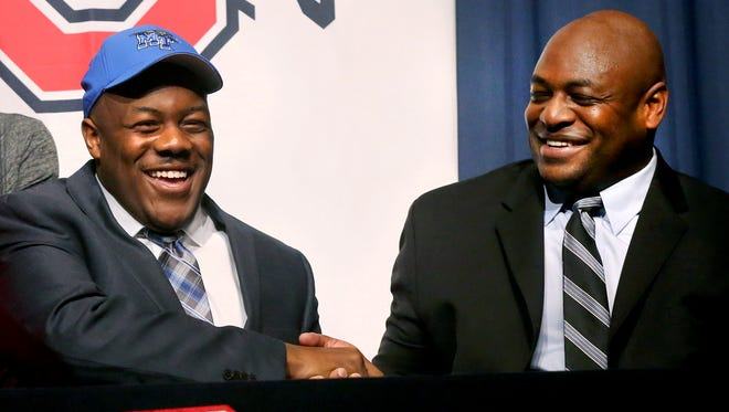 Oakland football player Ty Nix, left, shakes the hand of his father Tyrone Nix after Ty Nix signed with MTSU on, Wednesday. Tyrone Nix is the MTSU defensive coordinator.