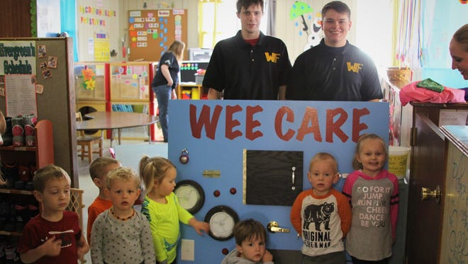 """Jake Trauernicht, right, and Jordan Shaw delivered the """"Busy Board"""" that was designed by Warrior Fabrication and Repair for children at Wee Care Child Center."""