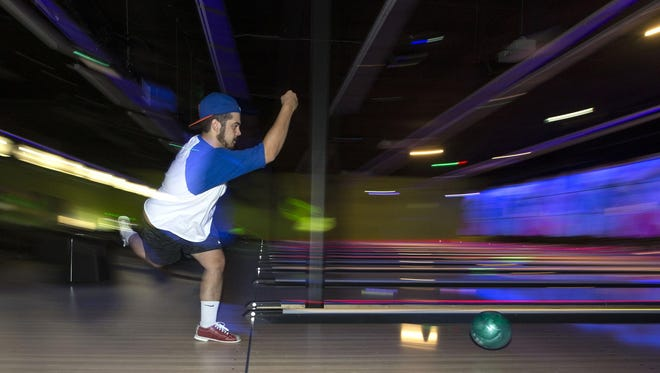 John Giove of Queen Creek breaks in the new bowling alley on opening day at Fat Cats.