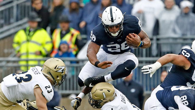 Penn State's Saquon Barkley (26) hurdles Akron's Alvin Davis (1) during the first half of an NCAA college football game in State College, Pa., Saturday, Sept. 2, 2017. Barkley has answered questions about whether he'll play in Penn State's bowl game or not, angering head coach James Franklin. (AP Photo/Chris Knight)