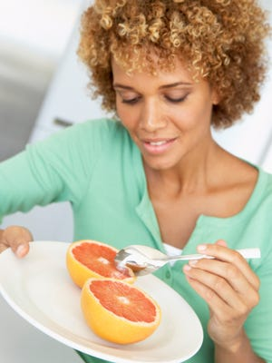Mid Adult Woman Eating Fresh Grapefruit