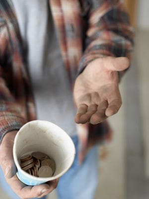 Stock photo of panhandler with change in cup.