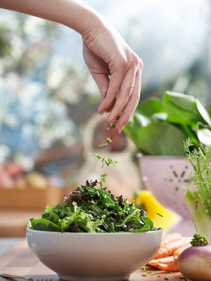 Woman pouring herbs into bowl of salad