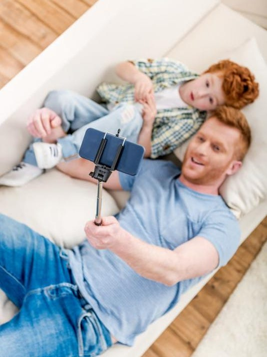 Smiling father and son lying on sofa and taking selfie with smartphone, family fun at home concept
