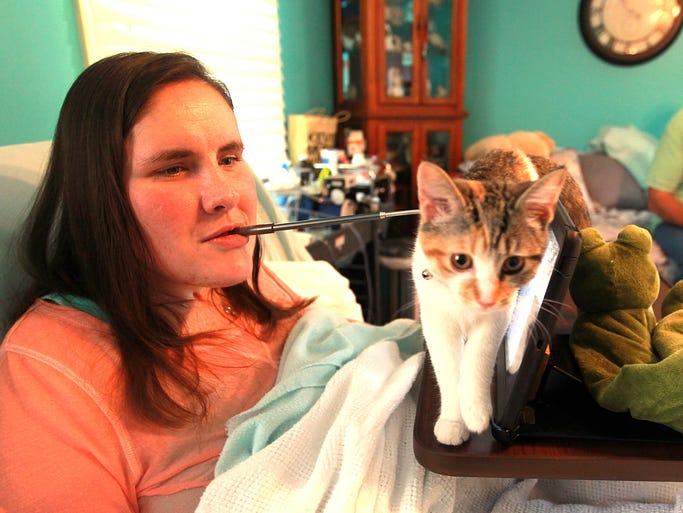 Alisha Waters' cat, Athena, walks in front of her iPad, as she uses a stylus in her mouth to operate it. Waters was rendered a quadriplegic last year when she was shot five times by her husband.