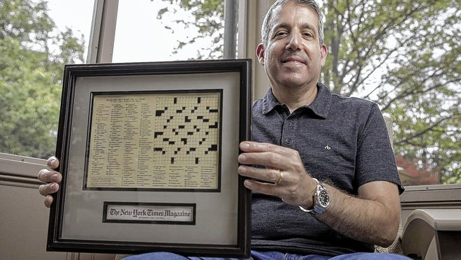 Crossword-puzzle constructor Seth Abel holds his first published puzzle in The New York Times Magazine from 2003 at his home in Bexley.