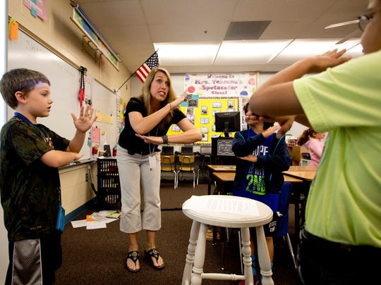"""Gateway Elementary School third-grade teacher Kerri Toscano takes part in a lesson recently. Toscano uses a teaching method called """"whole brain learning,"""" which implements physical activity as a teaching tool. On the left is student Curtis Couillard."""