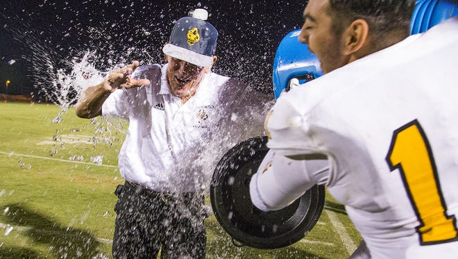 Marcos de Niza head coach Paul Moro is attacked with gatorade from his team after defeating Seton Catholic, Friday, October 14, 2016, and becoming the all-time high school coaching wins leader in Arizona.