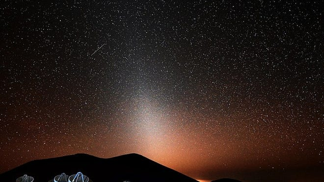 The zodiacal light, as seen from the dark Mauna Kea observatory site in Hawaii, Jan. 3, 2016. The sub-millimeter radio telescope array in the foreground was lit with a camera flash. [Photo by Stephen H. Keys (Own work) [CC BY-SA 4 (https://creativecommons.org/licenses/by-sa/4)], via Wikimedia Commons]