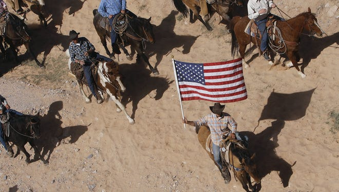 Jason Bean/AP The Bundy family and their supporters fly the American flag as their cattle is released by the Bureau of Land Management back onto public land outside of Bunkerville on April 12, 2014.