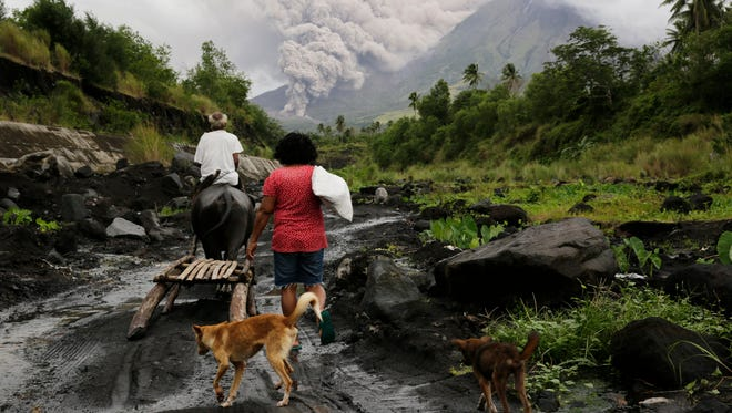 Filipino villagers walk along the slopes of rumbling Mayon Volcano as it spew ash in Legaspi city, Albay province, Philippines on Jan. 16, 2018.