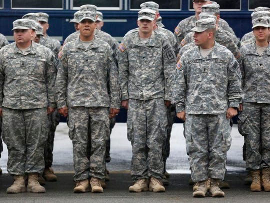 Members of the 222nd Military Police Company wait to be dismissed at the New York State Armory in Rochester on Saturday.