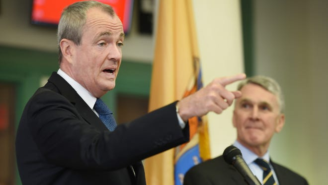 Gov. Phil Murphy speaks to the media as Kevin Corbett, who has been appointed executive director of NJ Transit, looks on during a press conference in New Brunswick on Jan. 30, 2018.