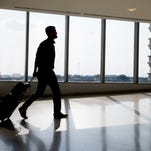 In this July 31, 2014 photo, a traveler passes through Philadelphia International Airport Thursday, in Philadelphia. Airlines continue to tinker with their frequent-flier programs, sometimes in ways that help business travelers but make it harder for occasional fliers to earn a free trip.  (AP Photo/Matt Rourke) ORG XMIT: NYBZ101