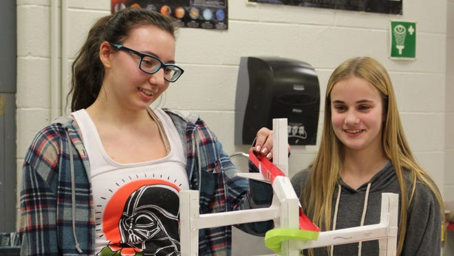 Warren Middle School seventh graders Hunter Miller (left) and Kaitlyn Loia use a marble to test their paper roller coaster on Jan. 8.