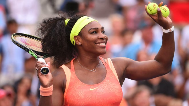 Serena Williams of the USA hits autographed balls to the crowd after beating  Madison Keys of the USA on day seven of the 2015 U.S. Open tennis tournament at USTA Billie Jean King National Tennis Center.