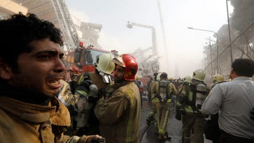 An Iranian fire fighter cry as other prepare as the iconic Plasco building collapses after a fire in Tehran, Iran, Jan. 19, 2017.