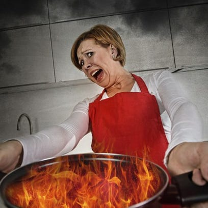 Woman holding pan on fire