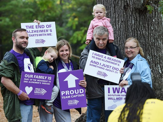 A group holds up their signs showing their dedication to ending Alzheimer's.
