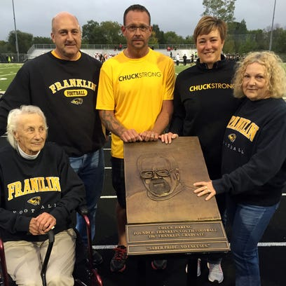 The Hareng family gathers around the plaque honoring the late Chuck Hareng in a ceremony at Franklin High School on Sept. 23. From left, mother Beatrice, sons Brad and Matt, daughter Julie and wife Corliss