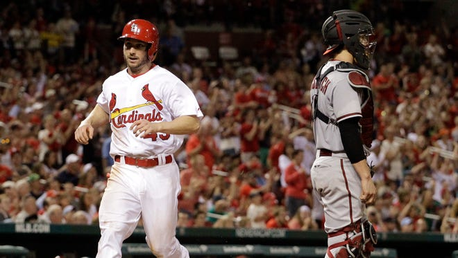 St. Louis Cardinals' Shane Robinson, left, scores on a single by Matt Carpenter as Diamondbacks catcher Tuffy Gosewisch stands by during the eighth inning of a baseball game Thursday, May 22, 2014, in St. Louis.