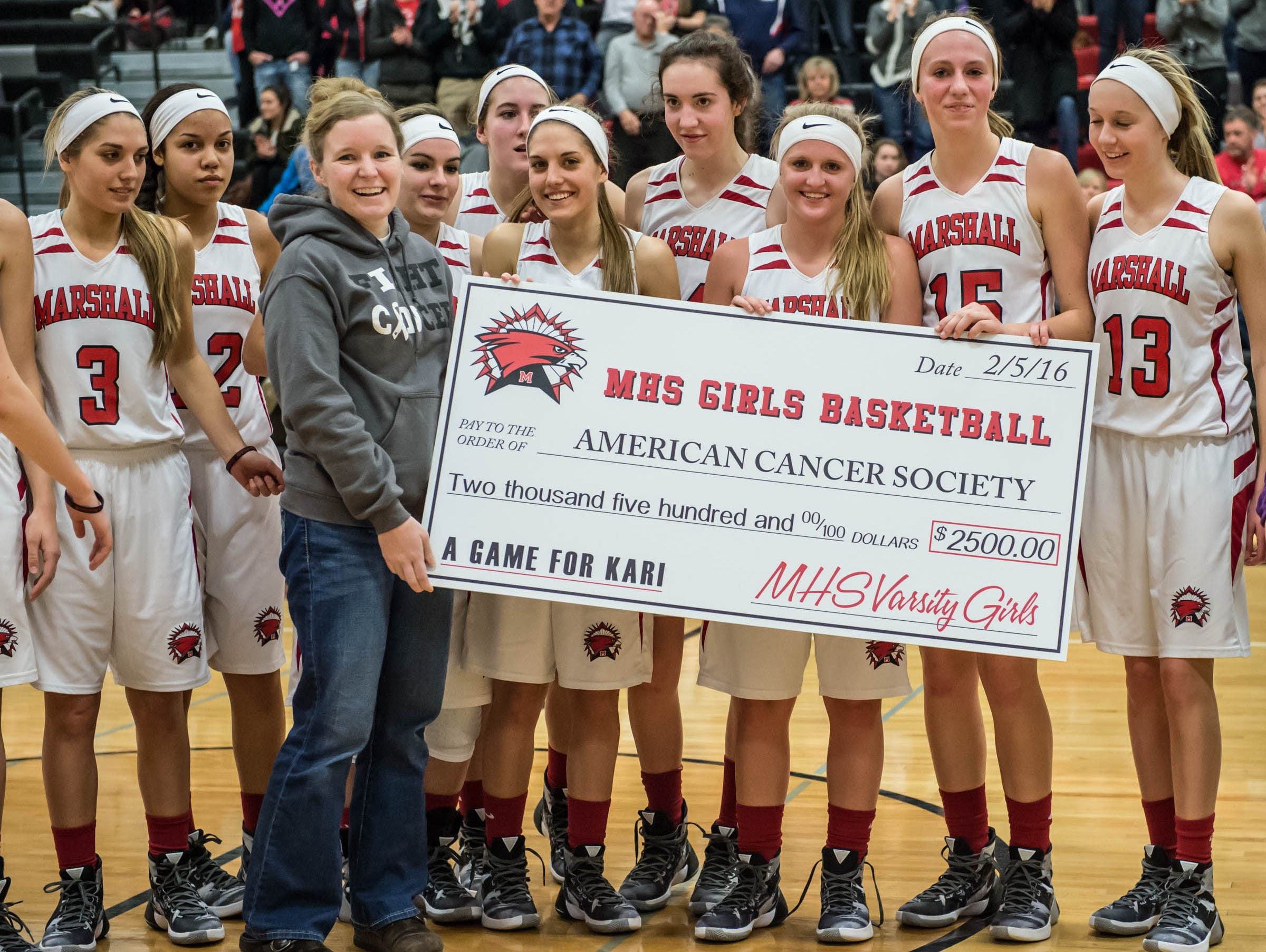 Kari Searles Jolink, 2001 graduate of Marshall High School and Marshall Middle School teacher received a fund rsising check from the girls varsity basketball Friday evening.
